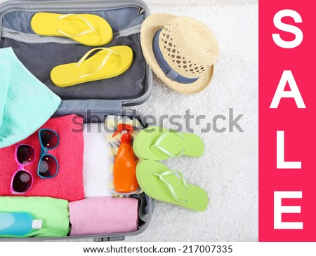 Concept of discount. Suitcase with things  for summer travelling - stock photo
