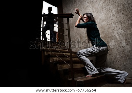 Concept of domestic abuse. Battered woman escaping from man silhouetted at the top of the stairs, in fear of more violence - stock photo