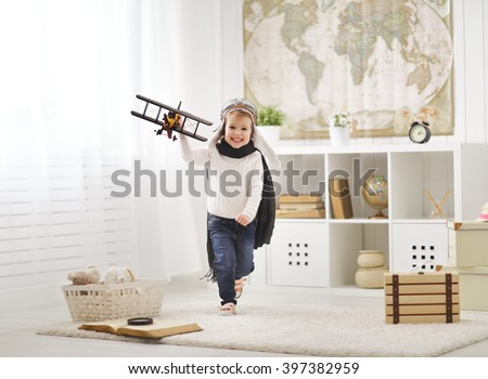concept of dreams and travels. happy child playing with an airplane pilot and runs the room