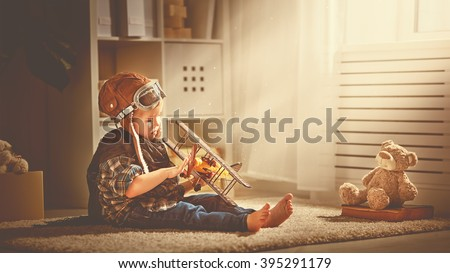 concept of dreams and travels.  pilot aviator child with a toy airplane plays at home in his room