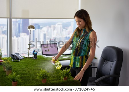 Concept of ecology and environment protection: Young business woman working in office with table covered of grass. She sprays water on plants and smiles - stock photo