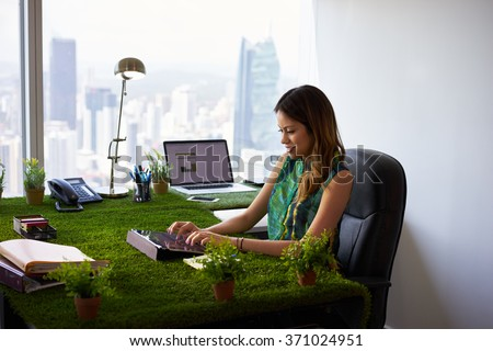 Concept of ecology and environment: Young business woman working in modern office with table covered of grass and plants. She types on tablet pc - stock photo