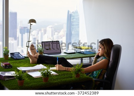 Concept of ecology and environment: Young business woman working in modern office with table covered of grass and plants. She writes on note pad with barefeet on desk - stock photo