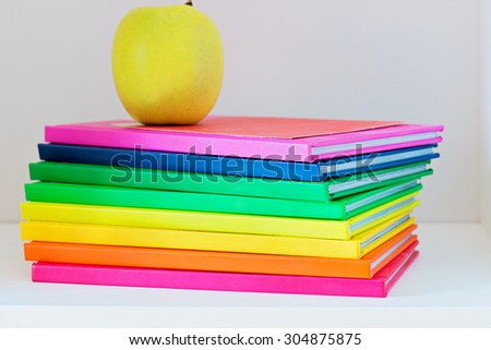 Concept of education. Apple sitting on top of a stack of school books - stock photo