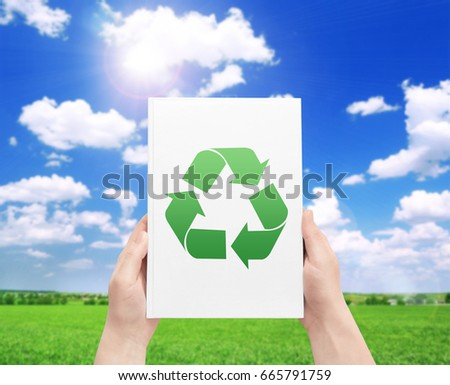 Concept of environmental conservation and protection. Woman holding paper with symbol of recycling and landscape on background