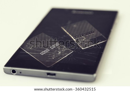 Concept of failed electronic payments - broken credit card on broken smart phone - stock photo