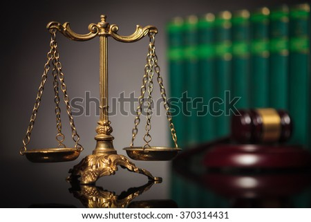 concept of fair law and justice, golden balanced scale in front of law books and judge's hammer - stock photo
