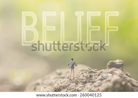 Concept of faith with a person stand in the outdoor and looking up the text over the sky in nature background. - stock photo