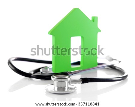Concept of family medicine - green house and stethoscope isolated on white background - stock photo