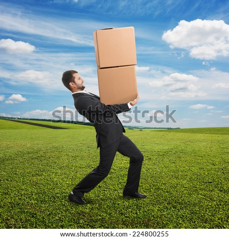 concept of fast delivery. young businessman carrying two heavy boxes at outdoor - stock photo