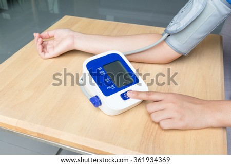 Concept of female press start button on blood pressure - stock photo