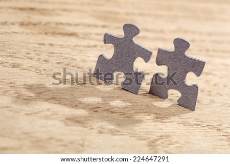 Concept of friendship: closeup of two jigsaw puzzle pieces on table. Shallow depth of field