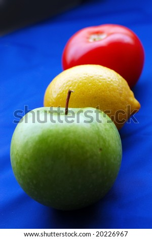 Concept of fruits representing traffic light on blue background (perspective with thin depth of field) - stock photo