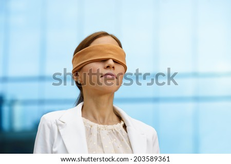 Concept of future and forecasting. Portrait of latina blindfolded businesswoman near office building - stock photo