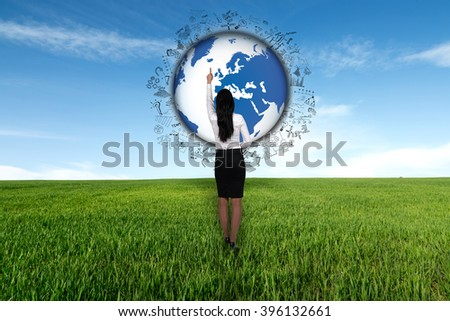 Concept of global business. Business woman stands on a meadow and points to the globe of business drawings. - stock photo