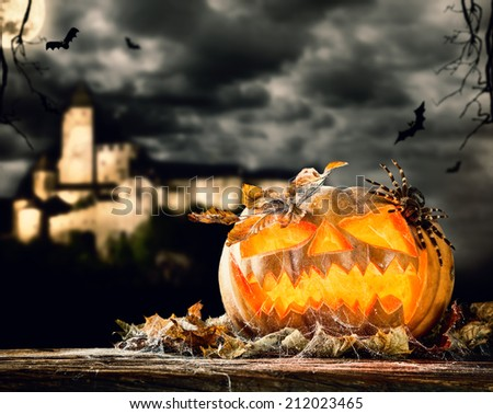 Concept of halloween pumpkin on wooden planks. Blur scary castle on background - stock photo