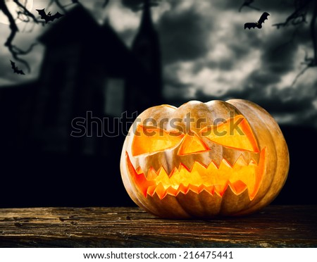 Concept of halloween pumpkin on wooden planks. Blur scary church on background - stock photo