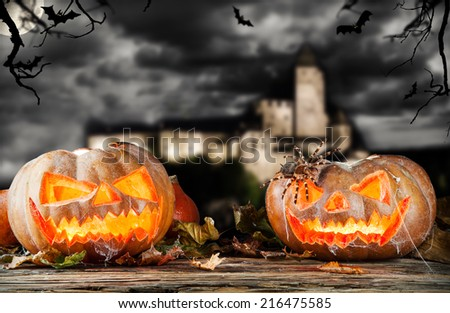 Concept of halloween pumpkins on wooden planks. Blur scary castle on background - stock photo