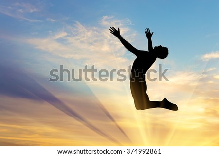 Concept of happiness and freedom. Silhouette happy man jumping on a sunset background