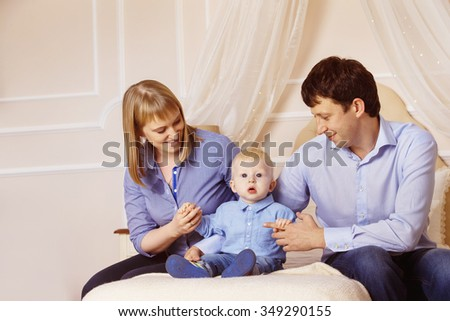 Concept of happy family. Father, mother and son are sitting together in bedroom at white background. - stock photo