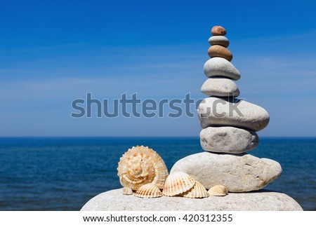 Concept of harmony and balance. Rock Zen of seashells on a background of summer sea - stock photo