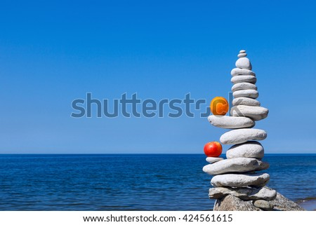 Concept of harmony and balance. Rock Zen with apple and  orange in the background of summer sea - stock photo