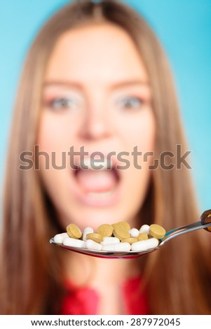 Concept of health care or abuse and addiction tablets. Young woman eating pills on a spoon on blue - stock photo