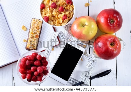 Concept of healthy food, accessories for recording diet: a smartphone, notebook, pen and measuring tape. Juicy berries and apples on a wooden table. - stock photo
