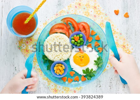 Concept of healthy food for child. Food art idea for kids breakfast egg and vegetable garnish tomato juice top view - stock photo