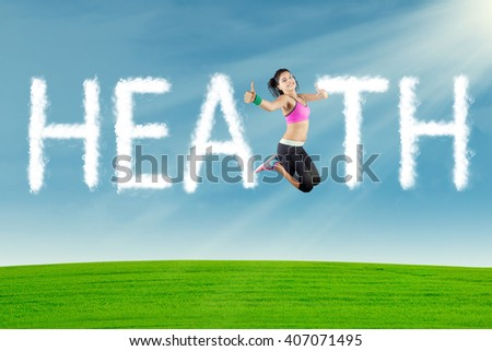 Concept of healthy life: Healthy Indian woman jumping at field with clouds shaped health text - stock photo