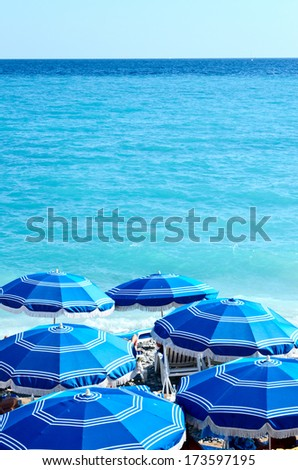 Concept of holiday blue beach with parasols - stock photo