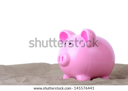 concept of holiday saving piggy bank in sand isolated on white