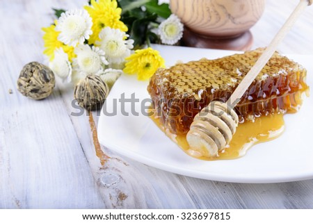 concept of honeycombs and flowers on white wooden background - stock photo