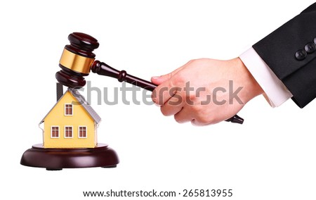 Concept of house sale with gavel in hand, isolated on white. Foreclosure
