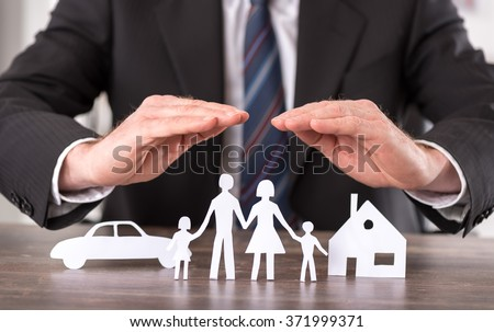 Concept of insurance with hands over a house, a car and a family - stock photo