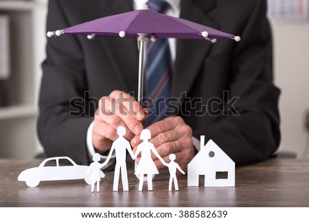 Concept of insurance with umbrella over a house, a car and a family - stock photo
