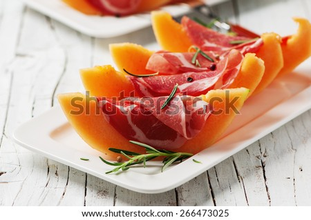 Concept of italian food with melon and prosciutto, selective focus - stock photo