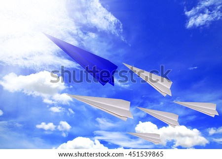 Concept of leadership as paper blue plane flying to the rising sun