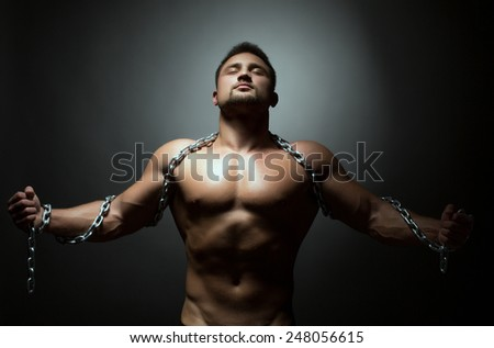 Concept of liberation. Naked man breaks chain - stock photo