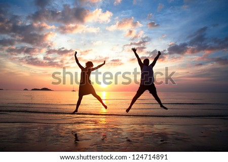 Concept of long-awaited vacation: Young couple in a jump on the sea beach at sunset. - stock photo