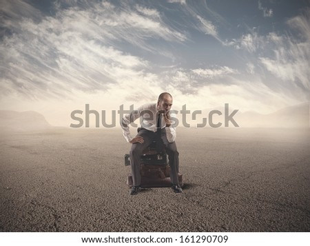 Concept of lost businessman confused sitting on suitcases - stock photo