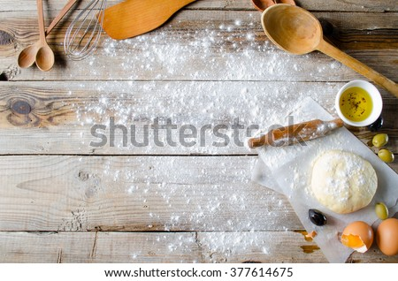 Concept of Making pie: Dough, rolling-pin, eggs, oil and wheat flour on wooden table. Food background top view. - stock photo