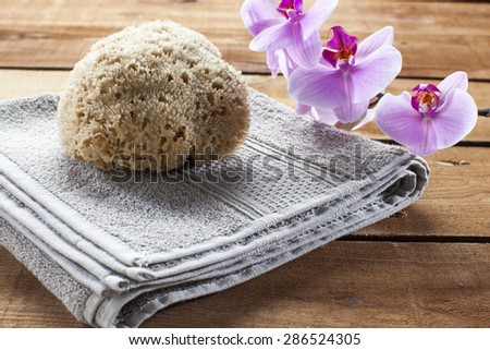 concept of massage and washing-up with towel, natural sponge and orchid flowers for wellbeing - stock photo