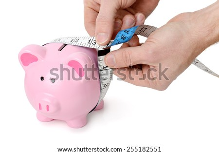 Concept of measuring your wealth, measuring tape around a piggy bank isolated on a white background - stock photo