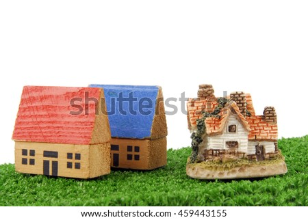 concept of miniature houses on grass - stock photo