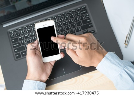 Concept of modern working style. Hand holding smartphone and other one on laptop keyboard - stock photo