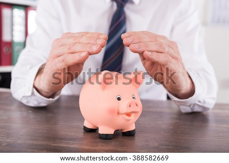 Concept of money protection with hands over a piggy