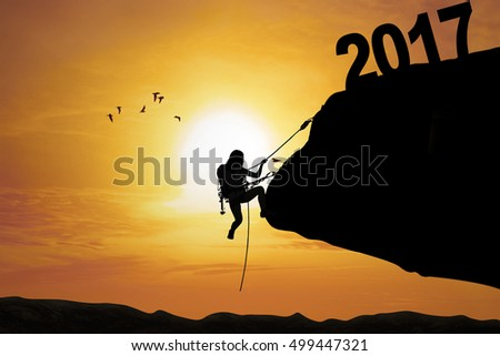 Concept of New Year 2017. Silhouette of a woman climbing a cliff with number 2017 at sunrise time