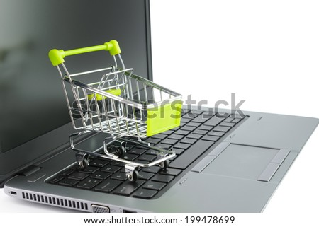 Concept of online shopping with miniature shopping cart on keyboard - stock photo