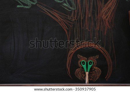 Concept of owl in hollow tree with scissors and chalk on black background - stock photo
